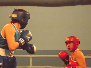 A women dressed in blue athletic attire and headgear (foreground) about to punch another woman wearing similar attire in red