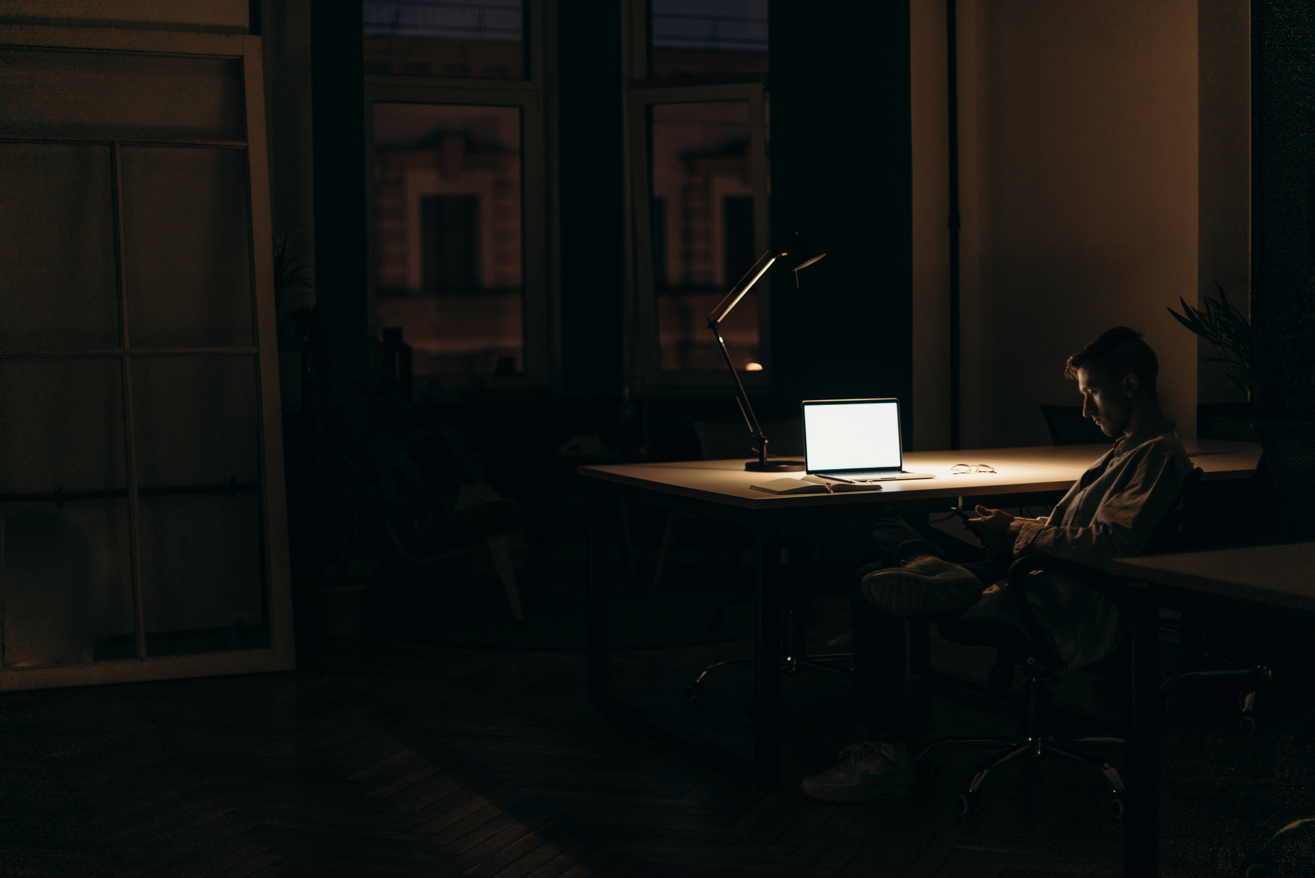 Man sitting in dark room with laptop